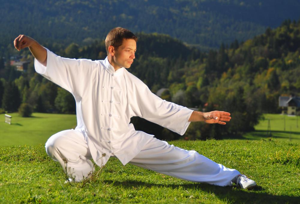 A tai chi instructor teaches students about the positions, postures, moves, forms, and poses used in tai chi.