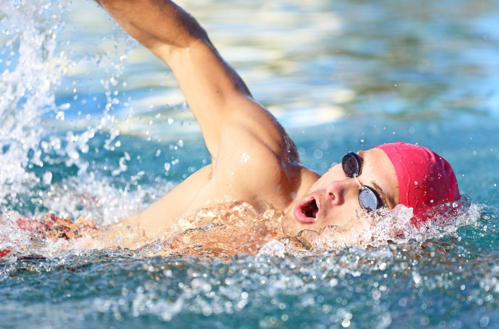 Swimmers swim laps while being timed to improve their performance.