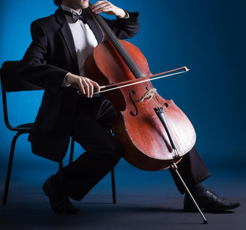 The cello is held between the players knees, with the neck against the player's left shoulder.