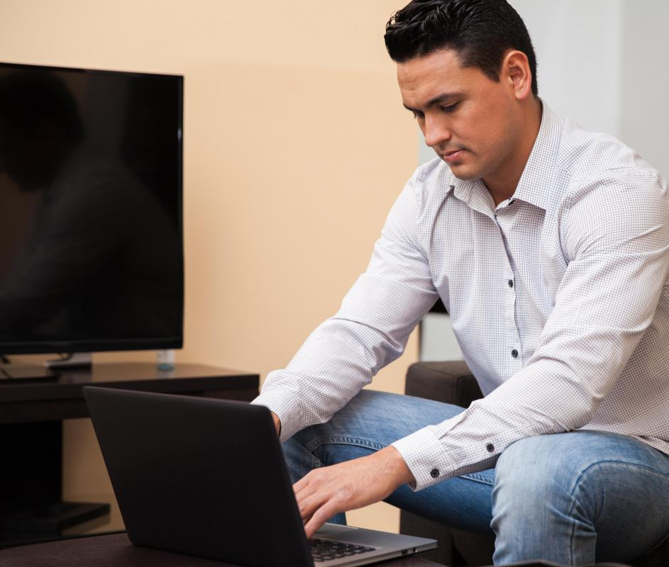 http://images.wisegeek.com/man-in-white-shirt-and-jeans-near-a-computer-and-television.jpg