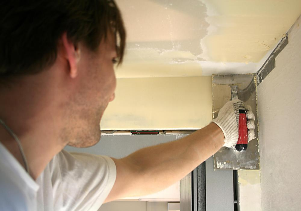 Spackling or joint compound is applied over the drywall patch to achieve a smooth finish.