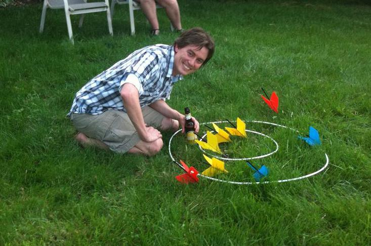 The game of lawn darts involves tossing large darts into circular targets.