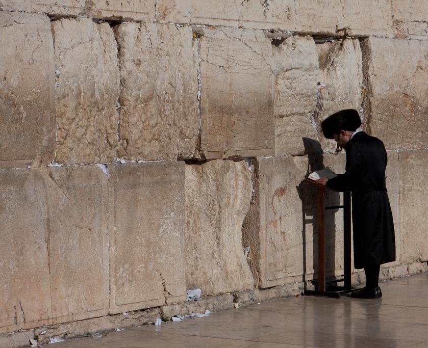 Man praying at the wailing wall. Notice the small pieces of paper pressed into the cracks between the stones.  These slips of paper typically contain prayers and are left by worshipers.