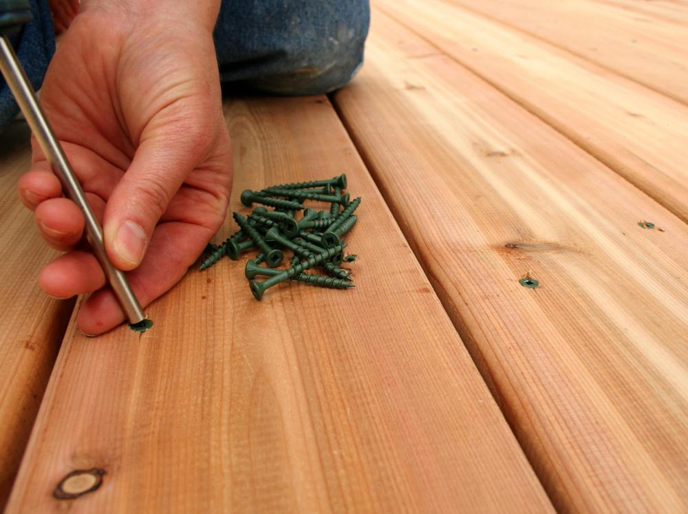 A man using deck screws to secure the boards of a deck.