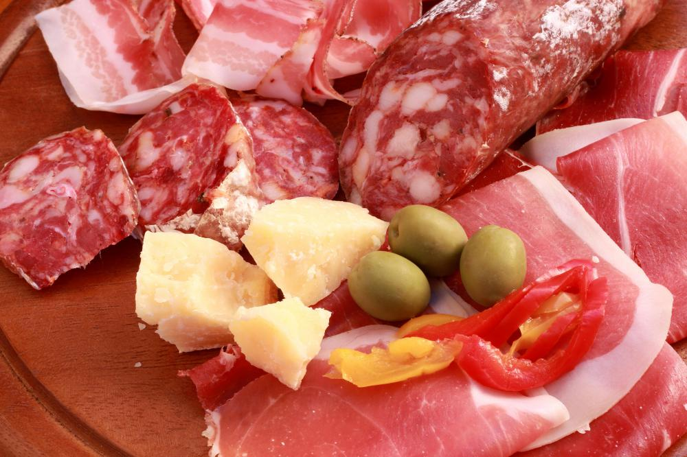 A variety of cured meats including salami and prosciutto as well as cheese, olives, and peppers is a common antipasto.