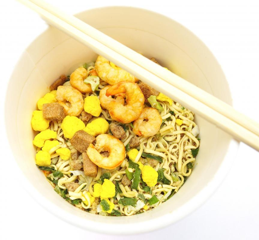 Shrimp and noodle dish stir-fried in a wok.