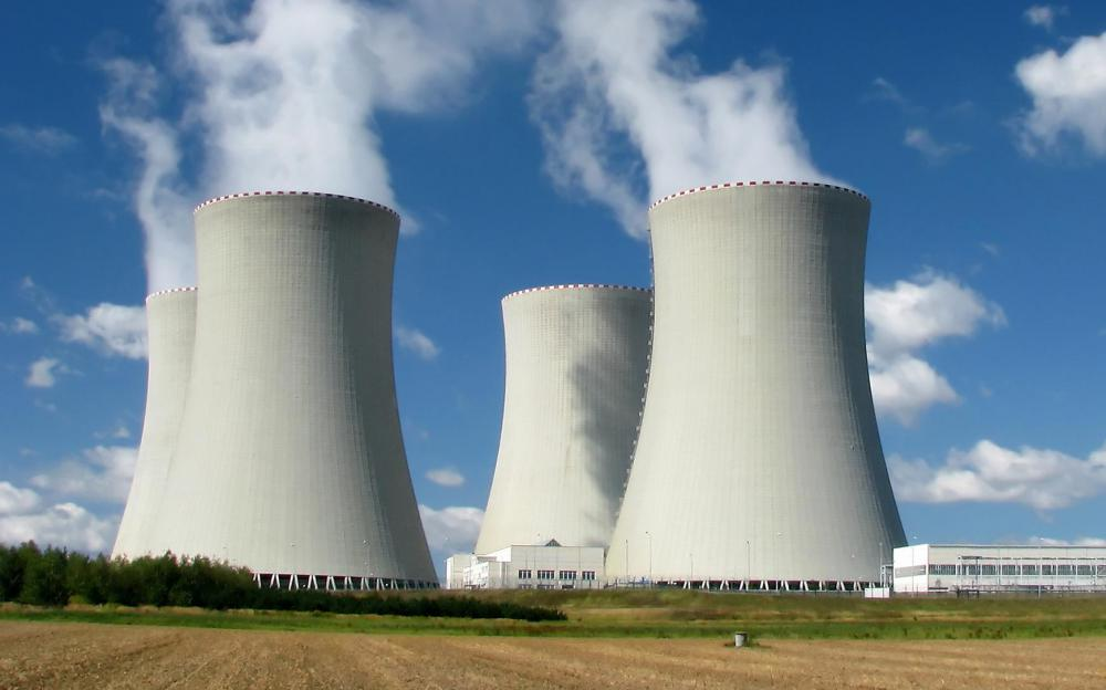A nuclear power plant uses fission to heat water into steam that, in turn, drives turbines that generate electricity.