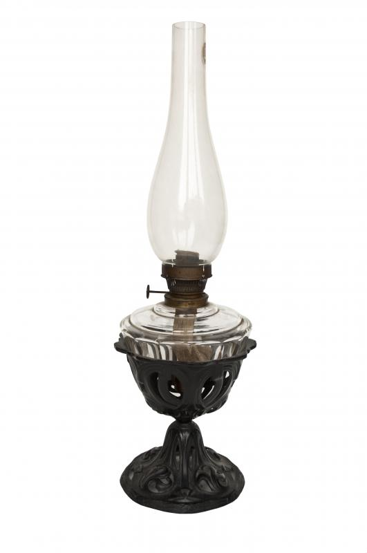 An oil lamp. Lamp oil is put in the bottom glass container, where it soaks into a wick which then burns in the glass chimney on top of the oil container.