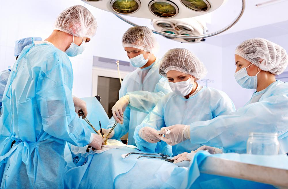 A scrub nurse assists doctors in the operating room.