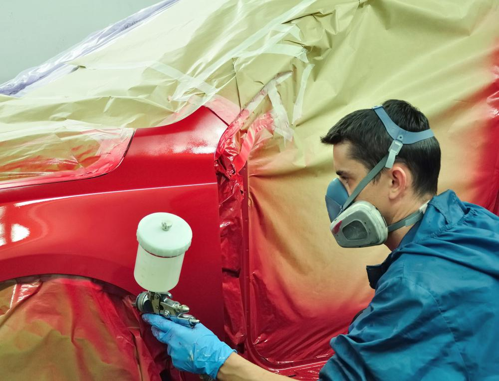 A man painting a car with flat paint.
