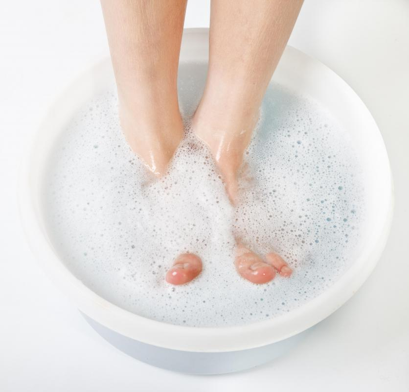 A person soaking her feet before a pedicure.