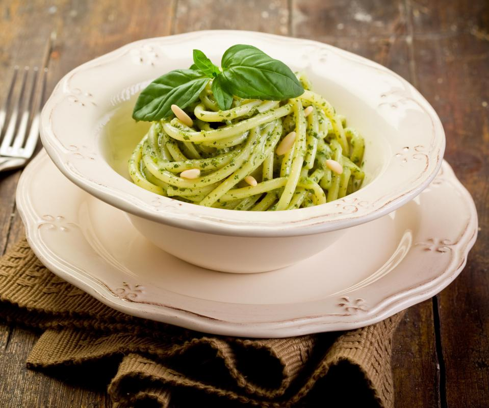 Pasta with pesto sauce, topped with pine nuts, is an easy vegetarian dish.