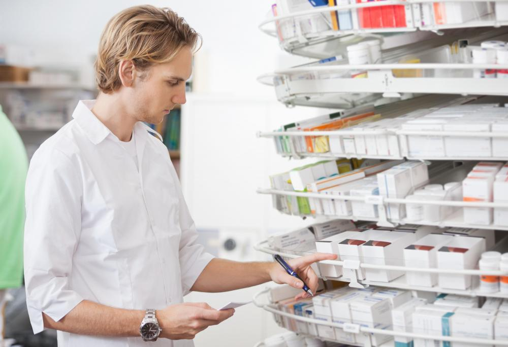 A pharmacy assistant properly sorts and stores medication.