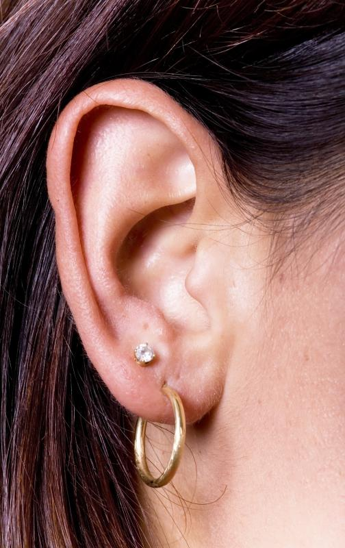 A woman wearing stud earrings and hoop earrings.