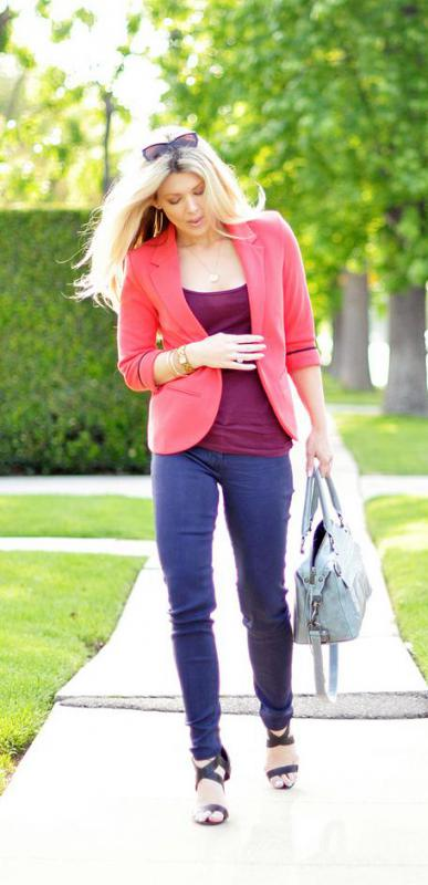 A fitted pink blazer with skinny blue jeans.