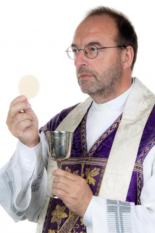 A priest with wine and a communion wafer.