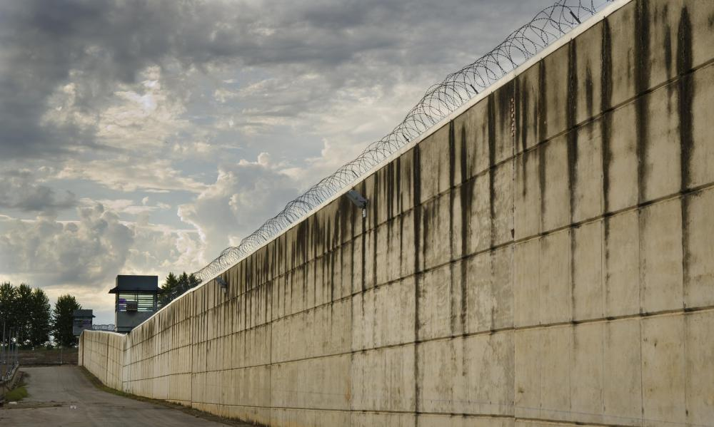Prison walls are often armed with barbed wire and electricity.