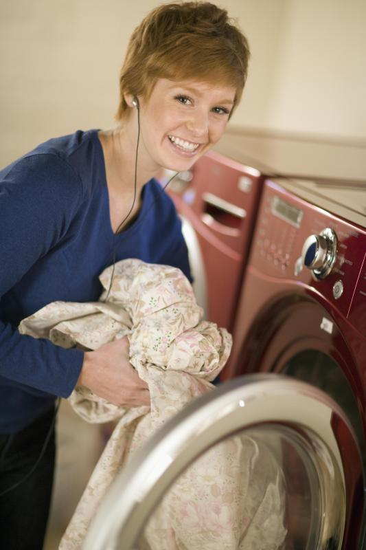 A woman pulling sheets out of a spin dryer.