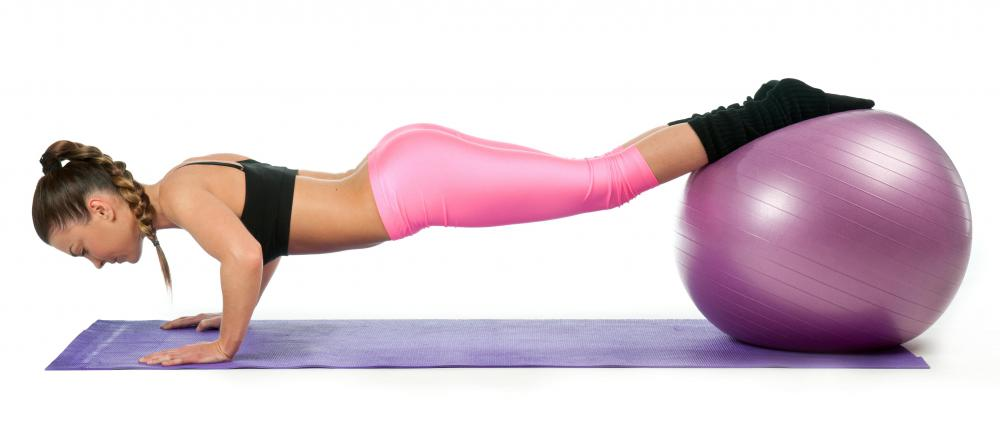 A woman does pushups with her feet elevated on an ab ball.