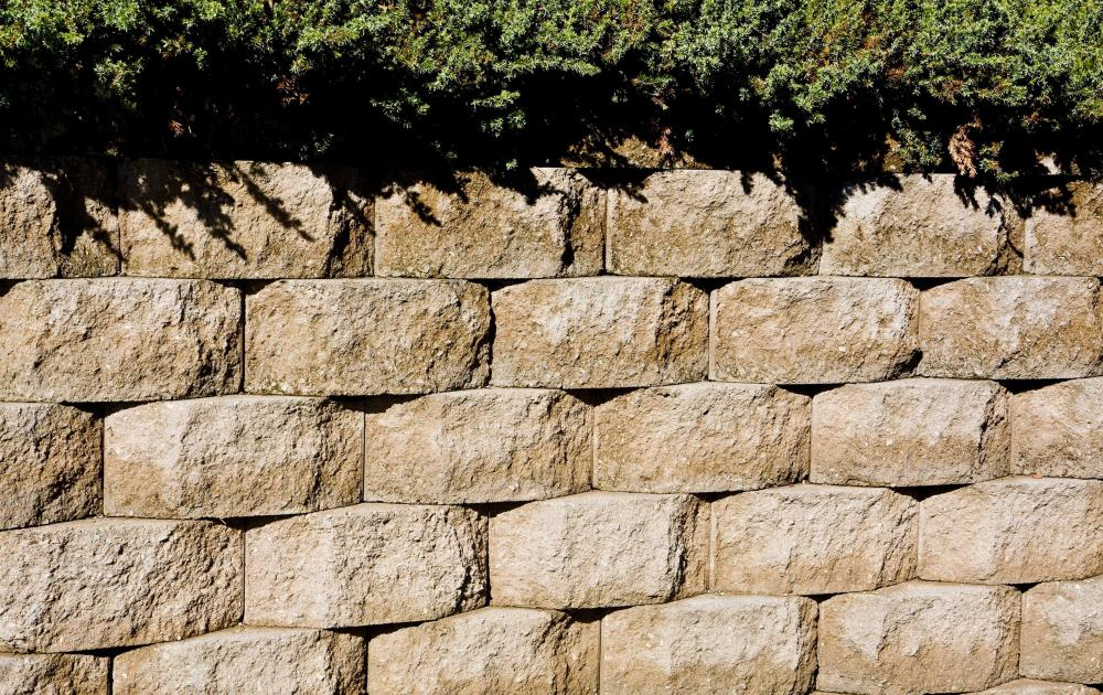 Retaining walls might use sturdy material, such as concrete blocks, to hold sloping ground in place.