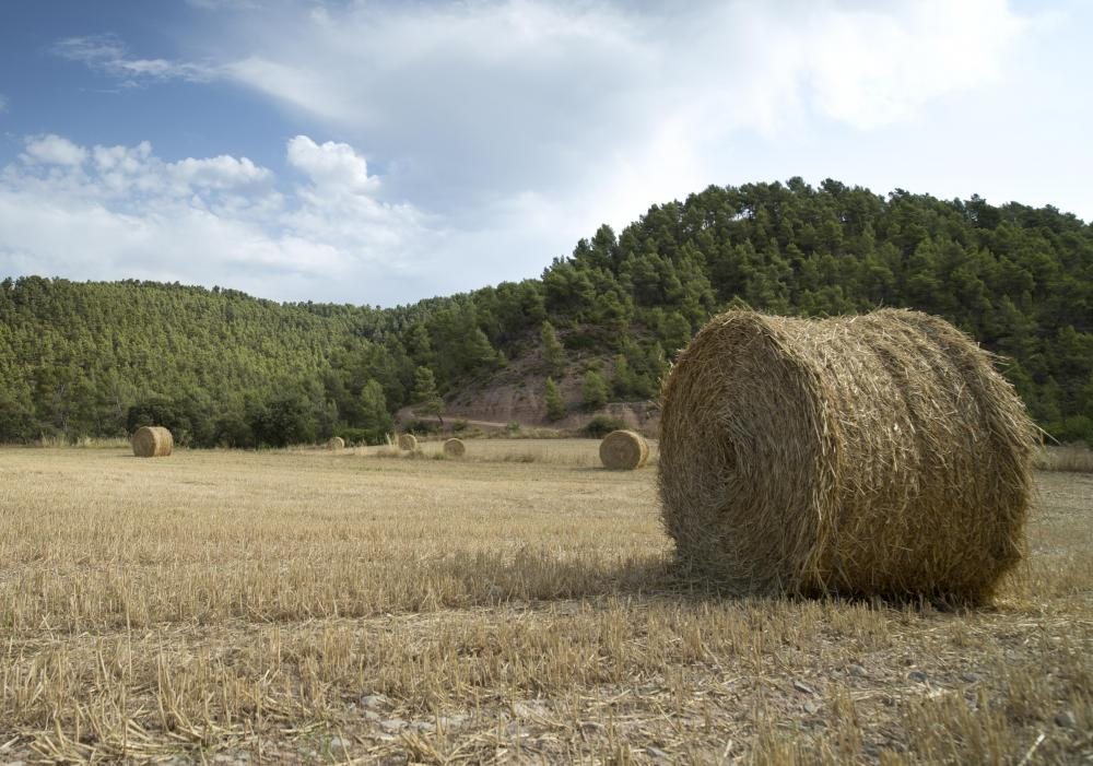 A round baler secures materials, such as straw, into a cylinderical bale.