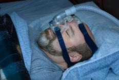 A man using a BiPAP breathing mask, a type of positive airway pressure device.