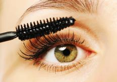 A woman applying mascara.