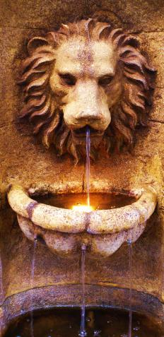 An outdoor wall fountain with a lion's face.