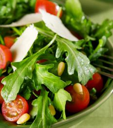 Arugula salad with cheese, tomatoes and pine nuts.