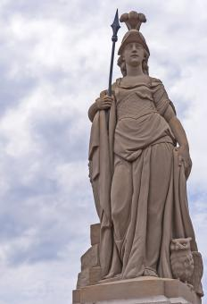 Statue of the Greek goddess Athena with an owl at her side.