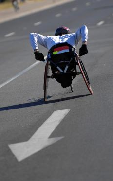 Athlete racing in a wheelchair with wheelchair restraints.