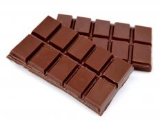 An enrober is used to coat candy bars with chocolate.