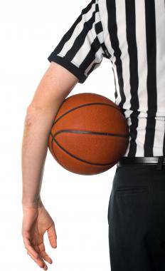 A basketball referee makes sure games are played by the rules.