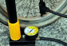 A bicycle pump attached to a tire at the valve stem.