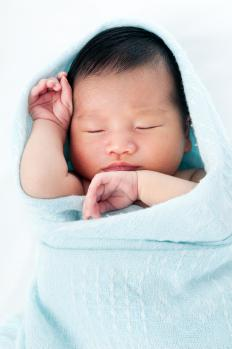 Infant swaddled in a blue receiving blanket.