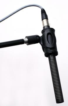 A boom microphone is mounted or attached to a pole or arm.