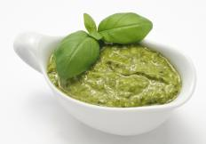 Bowl of pesto with basil leaves.