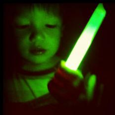 Boy playing with a glow stick, which uses bioluminescence to work.