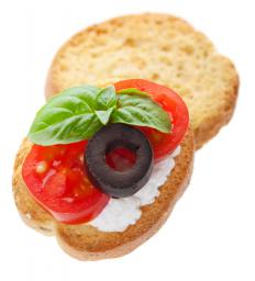 An appetizer with cheese, tomato, olive and basil.