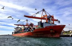 Container ships have their cargo offloaded by cranes at intermodal terminals.