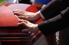 Mourners touching a casket at a funeral.