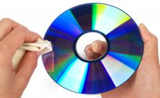 A person cleaning a CD with a microfiber cloth.