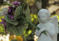 Many funeral flower arrangements are placed on the grave site in remembrance of the deceased.