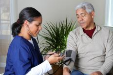 A medical professional listens for Korotkoff sounds while taking a blood pressure reading.