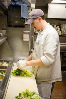 A food handler works in the back kitchen of a restaurant.