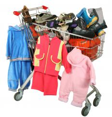 A shopping cart full of children's clothing, including some on hangers.