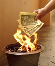 A person burning a facsimile of ancient Chinese money for a deceased couple.