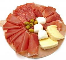 Classic antipasto platter including sliced prosciutto and salami along with olives and assorted varieties of cheese.