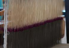 A jacquard loom utilizes an eye point needle to tightly weave threads to create fabric.