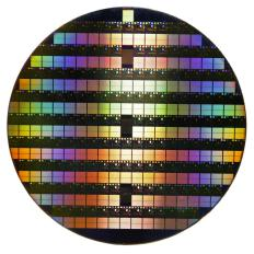 A silicon wafer is surfaced with a photoresist, which is a light-sensitive material.